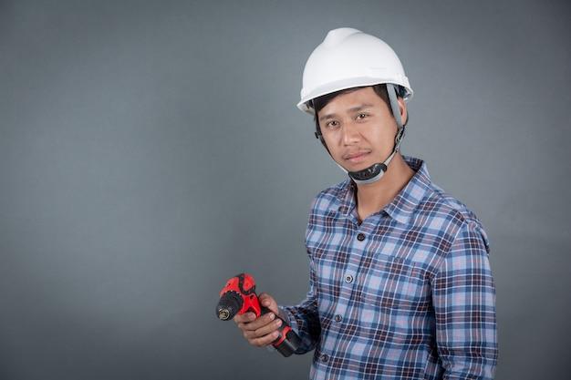 Builder tenant perceuse sur fond gris Photo gratuit