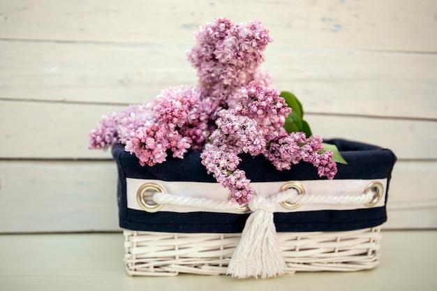 Buisson de lilas florissant syringa dans un panier blanc avec du bois vintage Photo Premium