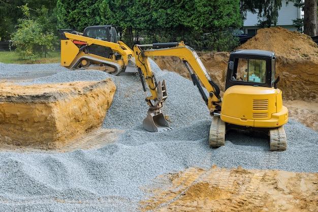 Un bulldozer sur roues remplit les travaux de fondation sur le chantier de construction. Photo Premium