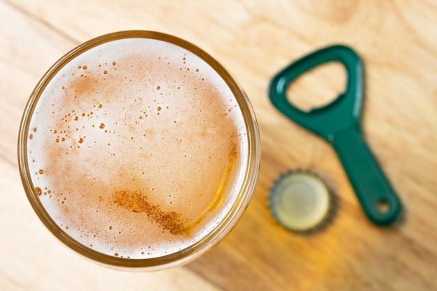 Bulle de bière froide et ouvreur vue de dessus sur table en bois Photo Premium