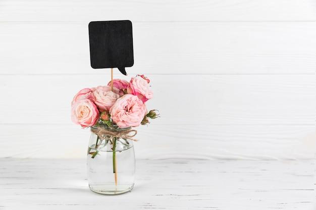 Bulle de dialogue noire en pot de verre rose sur fond en bois blanc Photo gratuit