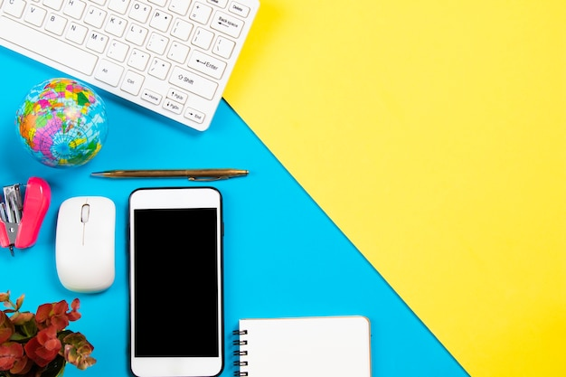 Bureau d'affaires avec papeterie et smartphone sur fond pastel Photo Premium