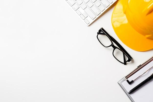 Bureau d'architecte avec outils, casque, ordinateur, lunettes et cahier. Photo Premium