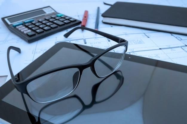Bureau d'architecte avec plans de construction, tablette, lunettes au studio d'architecte Photo Premium