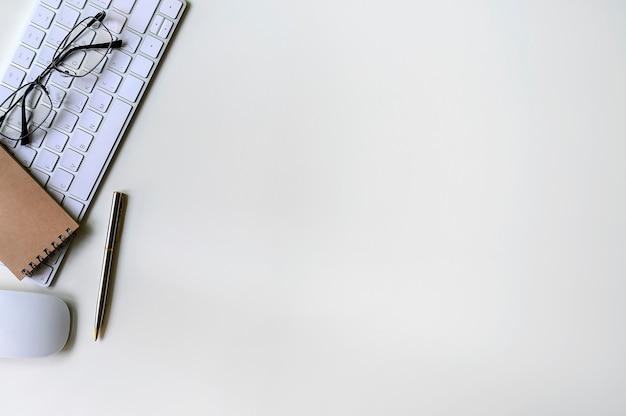 Bureau blanc avec fond blanc pour clavier, souris, stylo, lunettes et ordinateur portable Photo Premium