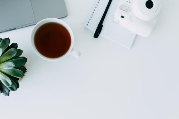 Bureau blanc avec ordinateur portable, ordinateur de bureau et ordinateur portable avec stylo, mini-caméra et tasse de thé. vue de dessus avec espace de copie, pose à plat Photo Premium
