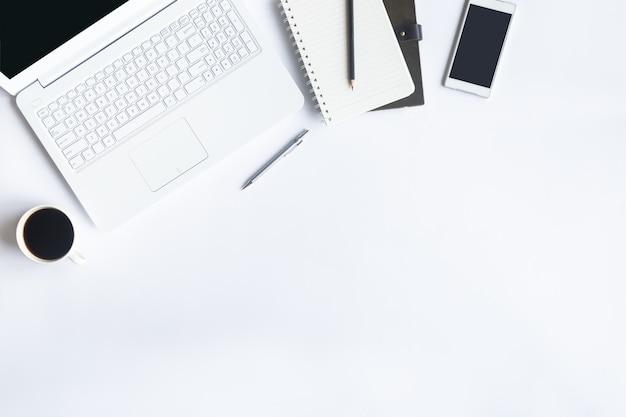 Bureau blanc à plat poser. vue de dessus sur les éléments essentiels de la table de bureau. Photo Premium