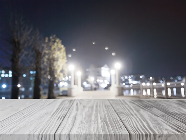 Bureau en bois gris en face de la ville illuminée la nuit Photo gratuit