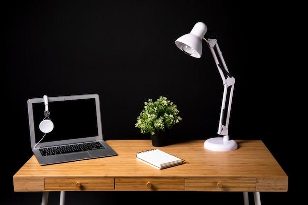 Bureau en bois avec ordinateur portable et lampe Photo gratuit