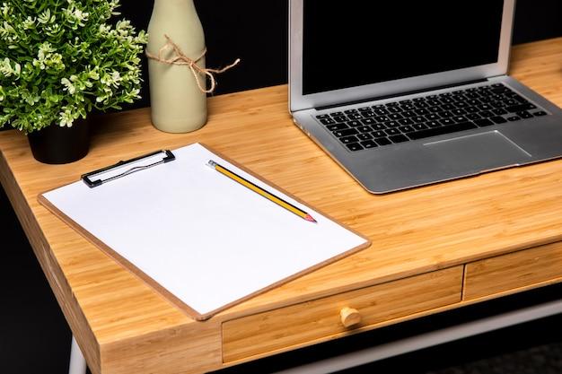 Bureau en bois avec presse-papiers et ordinateur portable Photo gratuit