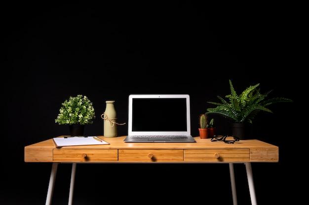 Bureau en bois simple avec ordinateur portable gris Photo gratuit