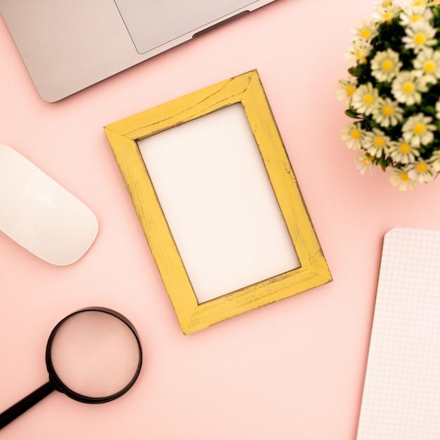 Bureau avec cadre photo vierge pour maquette sur fond rose Photo gratuit