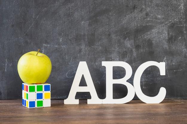 Bureau avec des caractères de l'alphabet rubiks cube et apple Photo gratuit