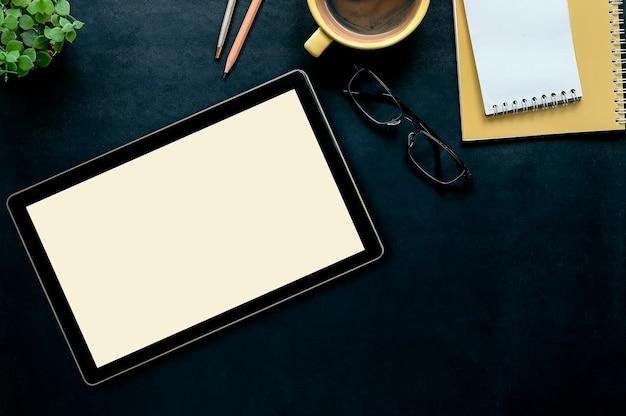 Bureau en cuir foncé avec tablette, tasse de café, crayon, lunettes et cahier jaune Photo Premium