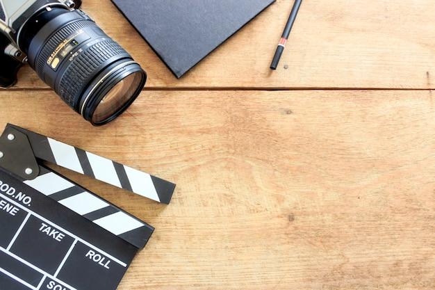 Bureau du réalisateur. clins, livre et appareil photo numérique sur table en bois Photo Premium