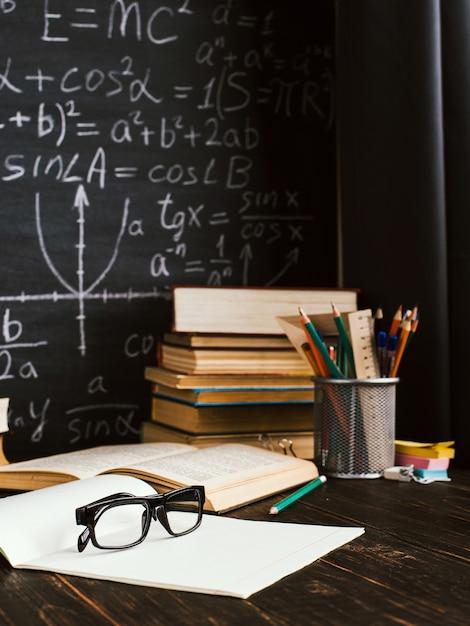 Bureau d'école dans la salle de classe, avec des livres sur fond de tableau avec des formules écrites Photo Premium