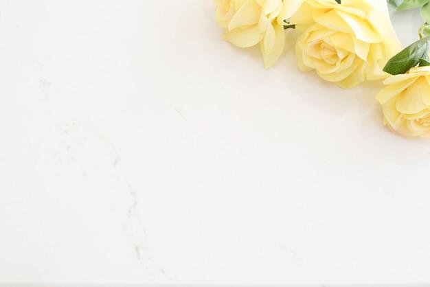 Bureau élégant en marbre clair avec roses jaunes Photo Premium