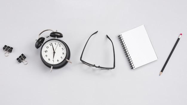 Bureau avec une horloge et des éléments de bureau Photo gratuit