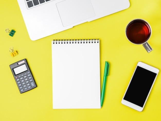 Bureau jaune vif créatif moderne avec ordinateur portable, smartphone Photo Premium