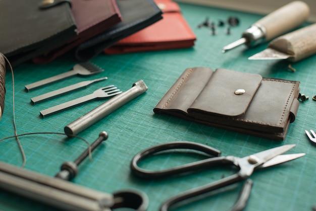 Le bureau de leathersmith. outils de travail en cuir sur une table de travail Photo Premium