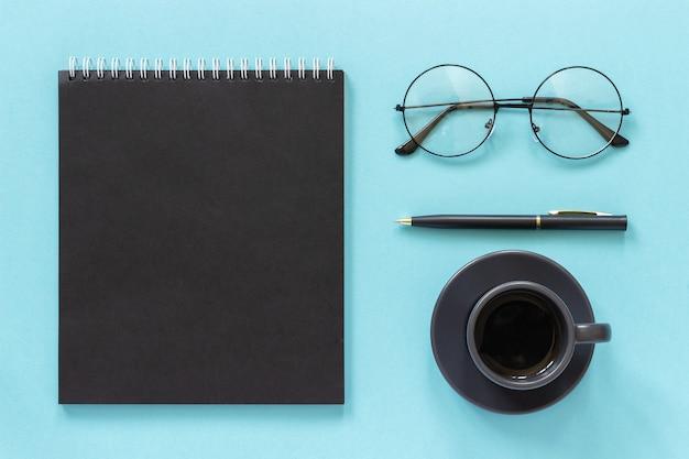 Bureau ou lieu de travail à domicile. bloc-notes de couleur noire, tasse de café, lunettes, stylo sur fond bleu Photo Premium