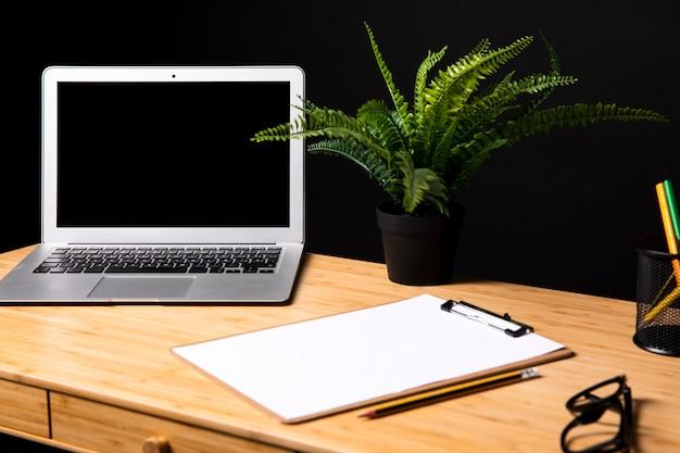 Bureau avec maquette d'ordinateur portable et de presse-papiers Photo gratuit