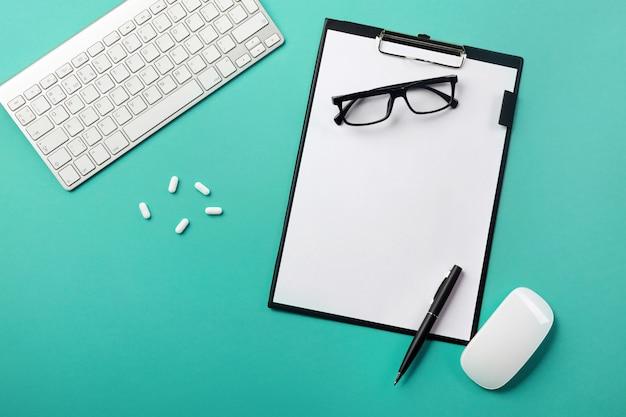 Bureau de médecin avec tablette, stylo, clavier, souris et pilules Photo Premium