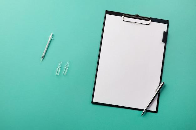 Bureau de médecin avec tablette, stylo, seringue et ampoules Photo Premium