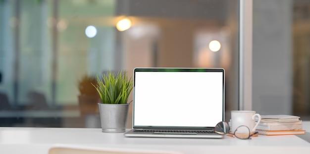 Bureau à la mode avec ordinateur portable à écran blanc Photo Premium