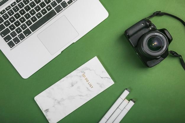 Bureau avec ordinateur portable et appareil photo Photo gratuit