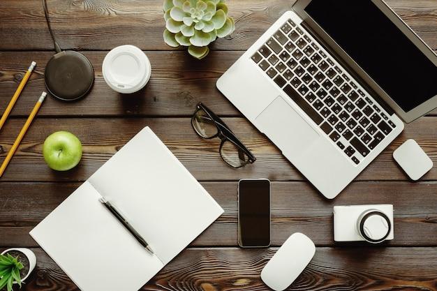 Bureau avec ordinateur portable, fournitures et pomme verte, vue de dessus Photo Premium