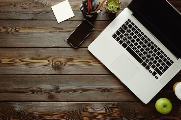 Bureau avec ordinateur portable, fournitures et pomme verte Photo Premium