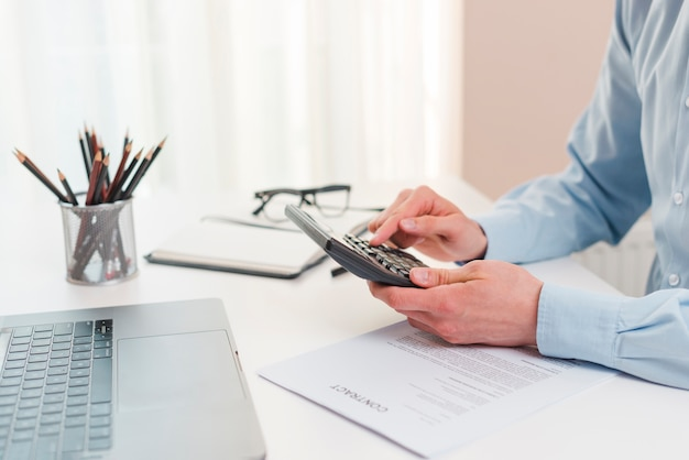 Bureau avec ordinateur portable et homme d'affaires Photo gratuit