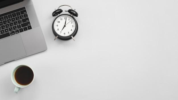 Bureau avec ordinateur portable et une horloge Photo gratuit