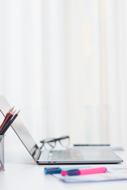 Bureau avec ordinateur portable et lunettes Photo gratuit