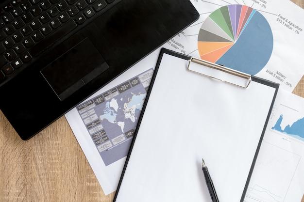 Bureau ordonné de l'homme d'affaires et des outils de travail avec la paperasse, ordinateur, appareils à écran tactile et papeterie sur une surface en bois, vue de dessus Photo Premium