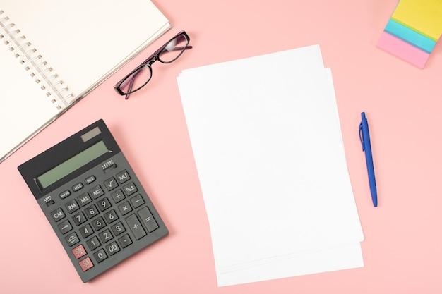 Bureau à Plat. Une Feuille De Papier Blanc Vierge Avec Un Stylo Est Au-dessus De La Table De Bureau Rose Avec Calculatrice Et Suppléments. Photo Premium