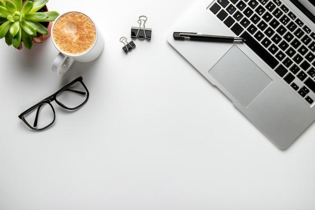 Bureau plat avec ordinateur portable et lunettes Photo gratuit