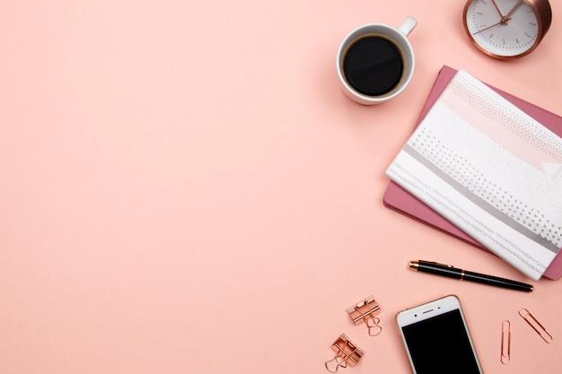 Bureau table bureau avec smartphone et autres fournitures de bureau sur fond rose. Photo Premium