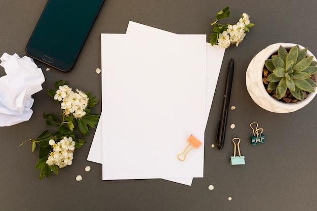 Bureau, table, maquette, smartphone, pappers vierges, cadre de fleurs de printemps. table de travail de bureau. espace de copie. Photo Premium
