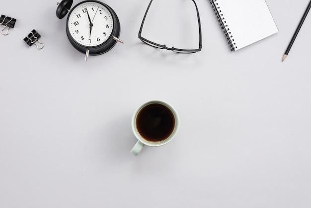 Bureau avec une tasse à café et des éléments de bureau Photo gratuit