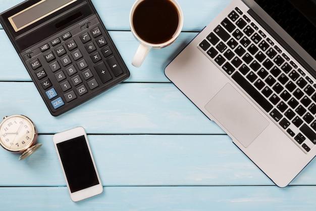 Bureau de travail avec ordinateur portable, calculatrice, téléphone moderne, café et réveil vintage sur une table en bois bleue. Photo Premium