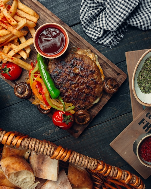 Burger d'agneau grillé sans pain servi avec poivrons grillés, frites, champignons, ketchup Photo gratuit