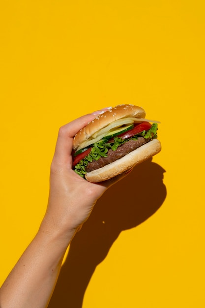 Burger appétissant en face de fond jaune Photo gratuit