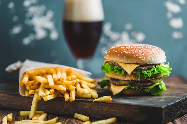 Burger aux pommes de terre et bière brune sur une planche de bois sur un fond bleu-gris Photo Premium