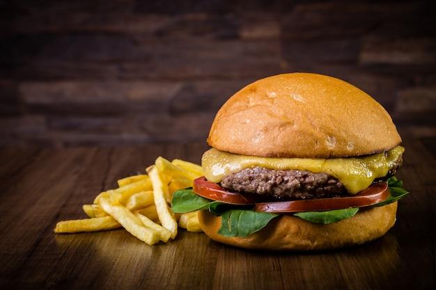 Burger de bœuf au fromage, feuilles de roquette et frites sur table en bois Photo Premium