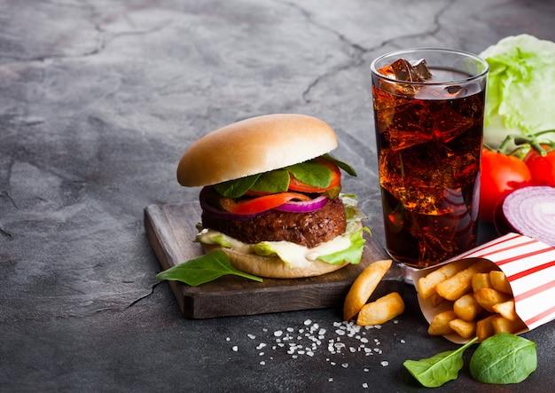Burger De Boeuf Frais Avec Sauce Et Légumes Et Verre De Boisson Gazeuse Au Cola Avec Frites De Pommes De Terre Frites Sur La Cuisine En Pierre. Photo Premium