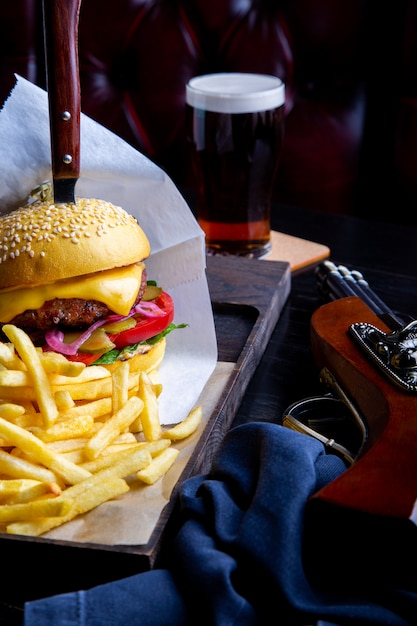 Burger de bœuf et frites sur la table dans le restaurant avec un verre de bière sur l'obscurité. cadre de restauration rapide moderne Photo Premium