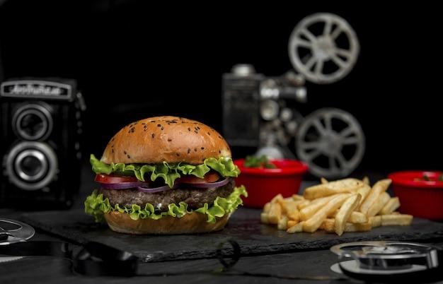 Burger de boeuf avec oignons émincés et tomates à l'intérieur du pain et des frites sur un plateau de pierre Photo gratuit