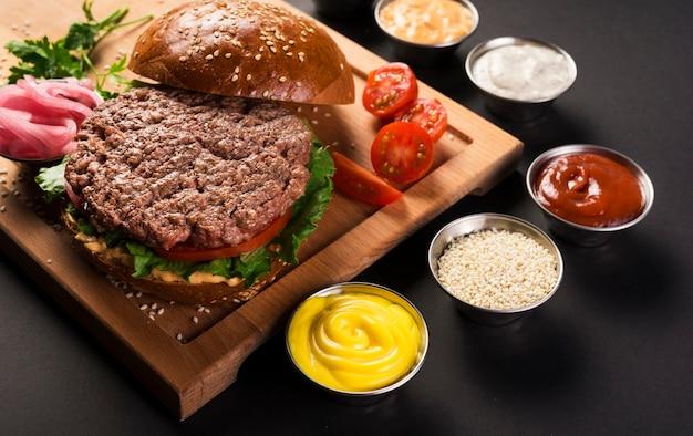 Burger de boeuf avec des sauces prêtes à servir Photo gratuit